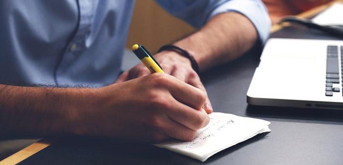 mano con penna che scrive su un foglio