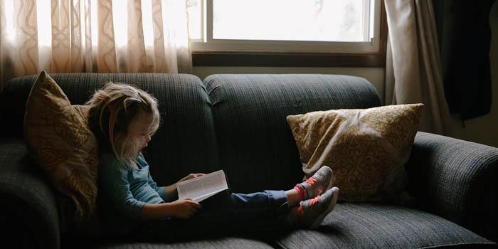 bambino che legge un libro sul divano